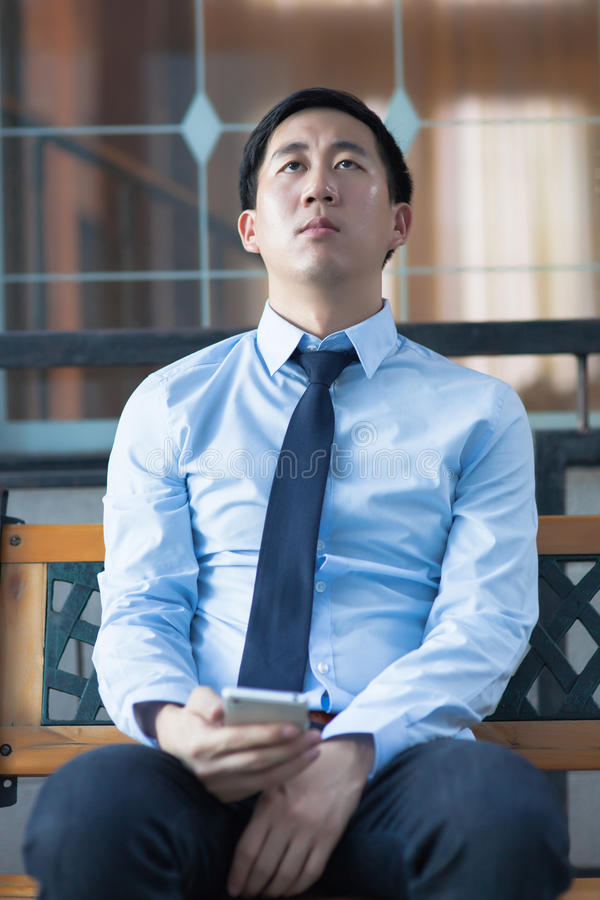 Бизнесмен вымотанный азиатом сидя в корпоративном здании стоковое изображение