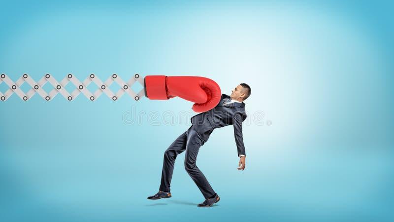 Бизнесмен в взгляде со стороны получает удар при большая красная перчатка бокса прикрепленная к металлу scissor рука на голубой п стоковые изображения