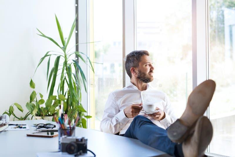 Бизнесмен в его офисе, имеющ пролом, выпивая кофе стоковое фото rf