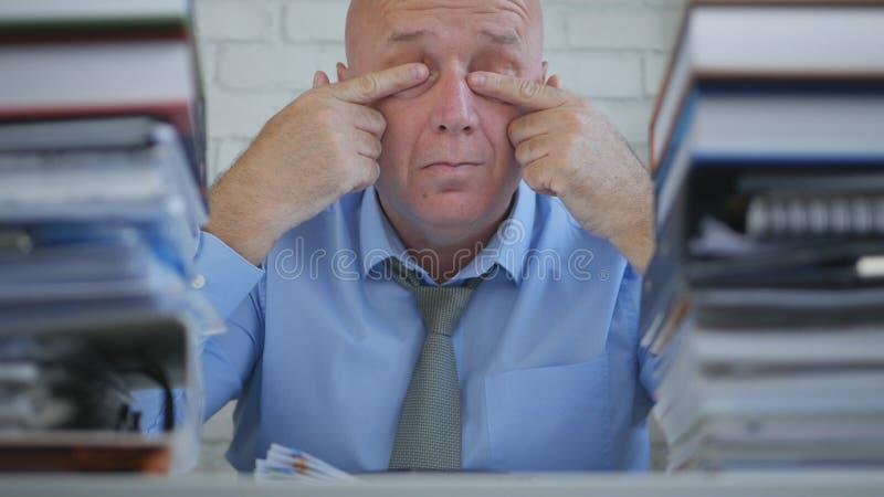 Бизнесмен в комнате офиса тереть его уставшие глаза с руками стоковое изображение