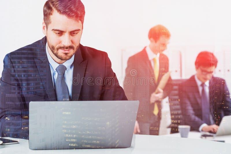 Бизнесмен в костюме работая на столе офиса перед ноутбуком пока 2 других коллеги позади обсуждают проект Концепция стоковая фотография rf