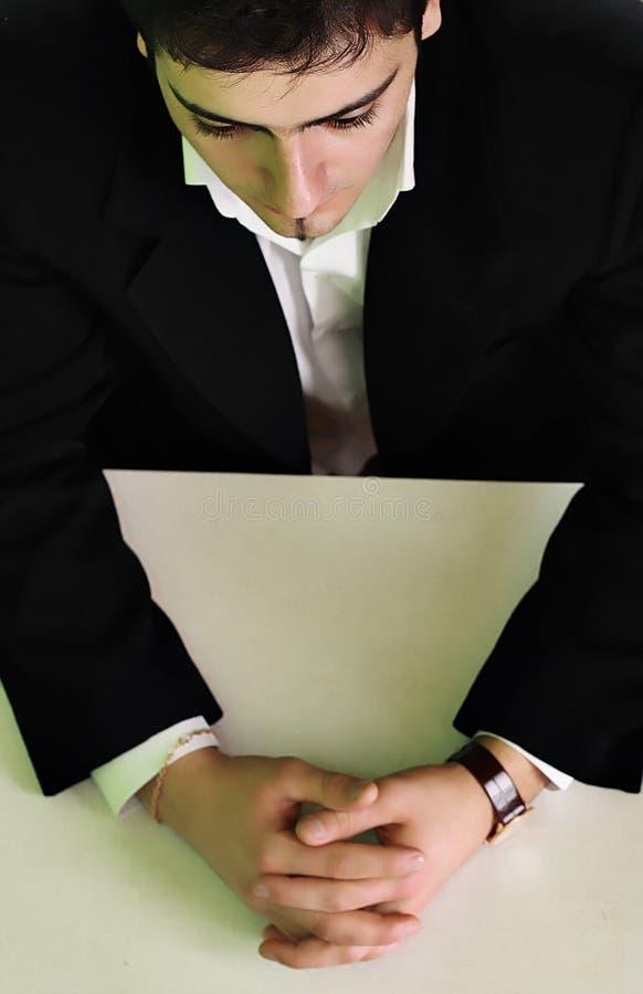 Бизнесмен в костюме сидит на таблице Стоковые Фото