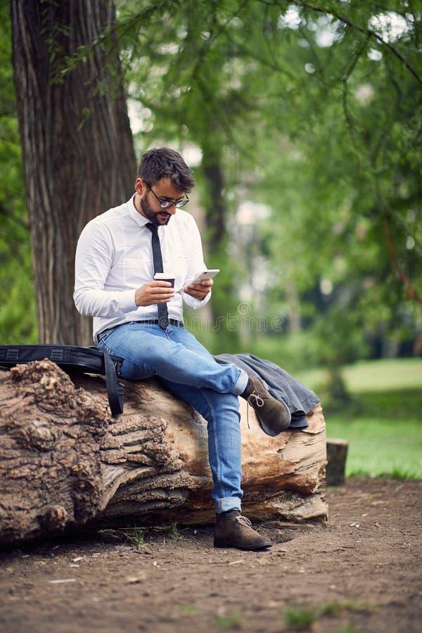 Бизнесмен в кофе парка работая и выпивая стоковые фото