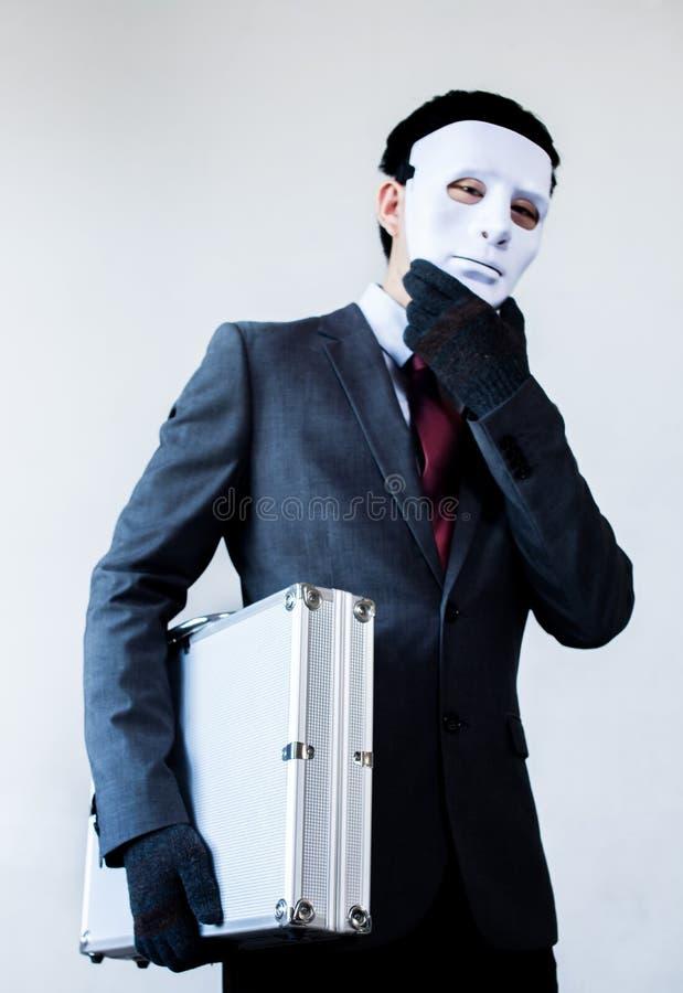 Бизнесмен в маске маскировки крадя конфиденциальный чемодан стоковые изображения rf