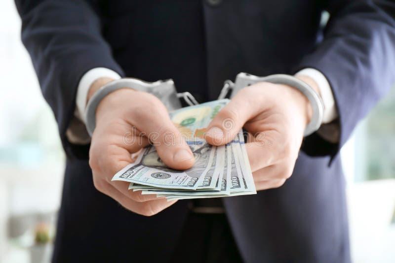 бизнесмен в наручниках держа взятку стоковая фотография