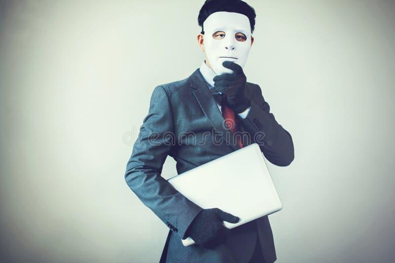 Бизнесмен в перчатках белой маски нося и компьютере красть и цифровая информация - очковтирательство, хакер, похищение, злодеяние стоковое фото