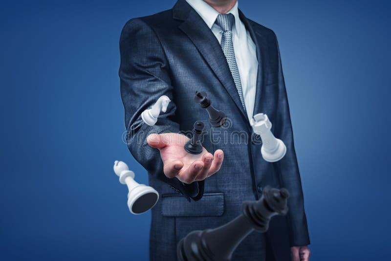 Бизнесмен в положении костюма с только верхн-телом видимым, держащ, что его рука вне если достигла chesspieces плавая внутри стоковая фотография