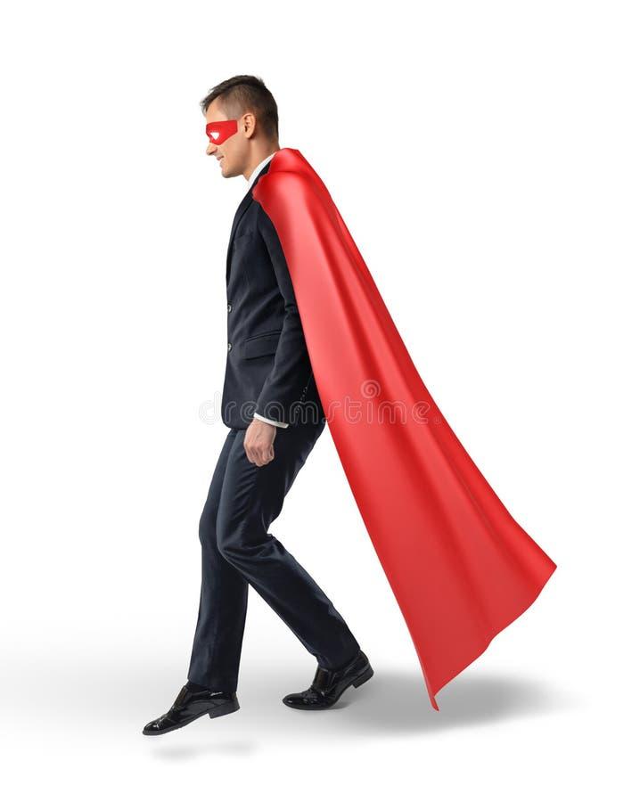 Бизнесмен в пропуская красной накидке шагая на незримую лестницу передний двигать стоковое изображение
