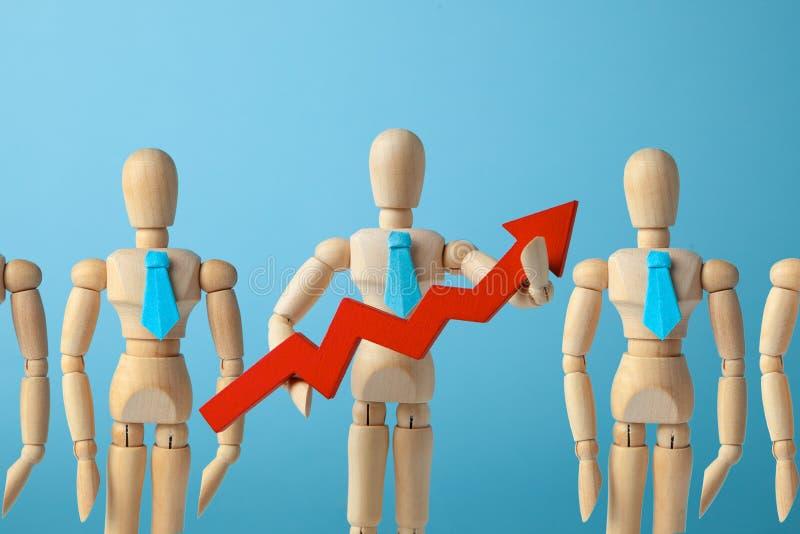Бизнесмен в связи держит красную стрелку вверх на голубой предпосылке Выбор хорошего руководителя от толпы работников стоковые изображения