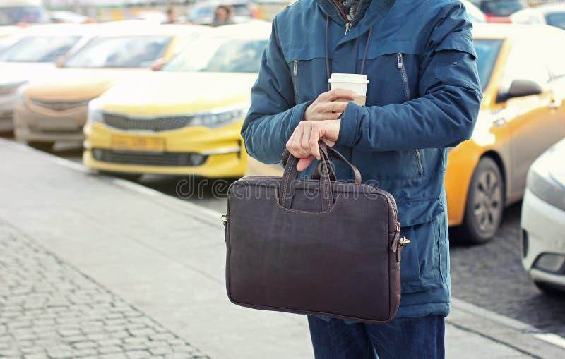 Бизнесмен в случайной куртке с кожаной сумкой и чашкой кофе стоит на дороге города с такси на заднем плане и подготавливает стоковое изображение