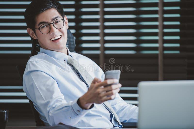 Бизнесмен в стеклах сидя на столе офиса с компьтер-книжкой стоковое фото