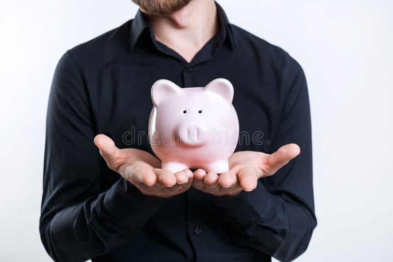 Бизнесмен в черной рубашке держа копилку Сохраняя деньги стоковое изображение rf