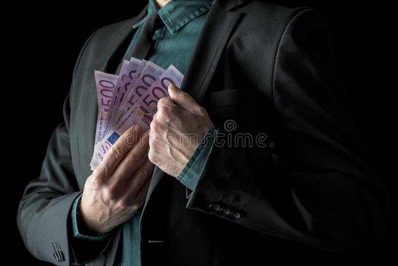 Бизнесмен в черном костюме держа 500 счетов евро стоковые фото