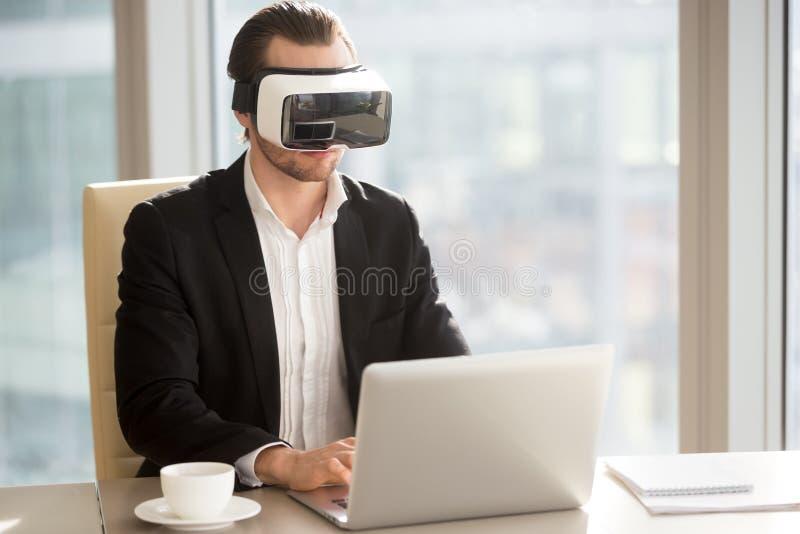 Бизнесмен в шлемофоне VR выполняя испытание применения по compute стоковое фото