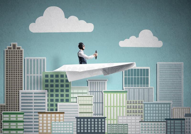 Бизнесмен в шляпе авиатора сидя в плоскости бумаги стоковые фотографии rf