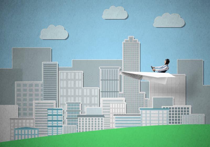 Бизнесмен в шляпе авиатора сидя в плоскости бумаги стоковое изображение