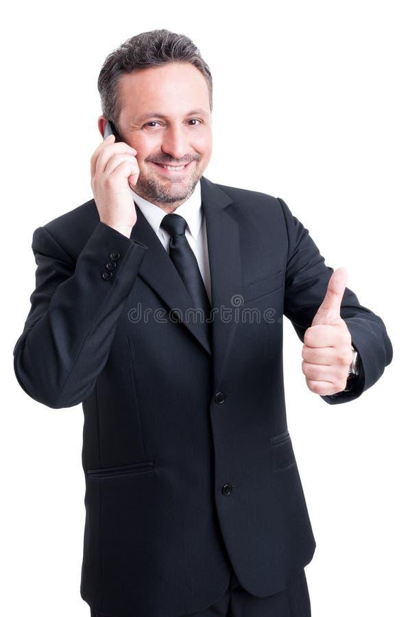 Бизнесмен говорит на телефоне и показывает большой палец руки вверх стоковые изображения rf