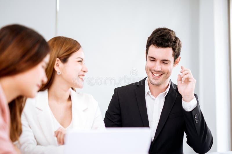 Бизнесмен говоря и усмехаясь Молодая команда сотрудников делая большее обсуждение дела в современном офисе Концепция людей сыгран стоковая фотография rf