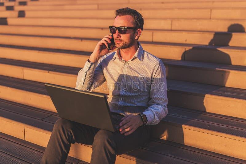 Бизнесмен говоря на мобильном телефоне и используя ноутбук пока сидящ на лестницах outdoors стоковые фото