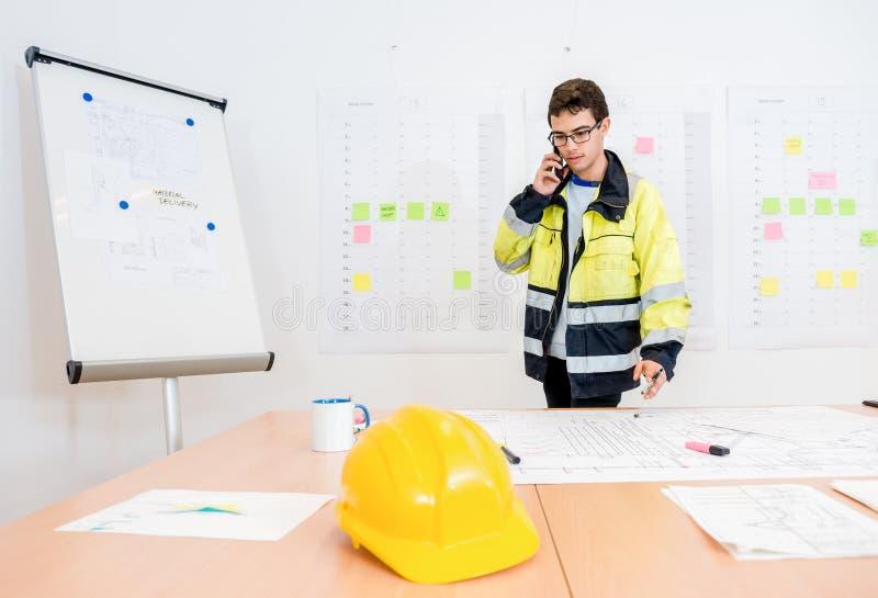Бизнесмен говоря на мобильном телефоне на таблице офиса стоковые фото