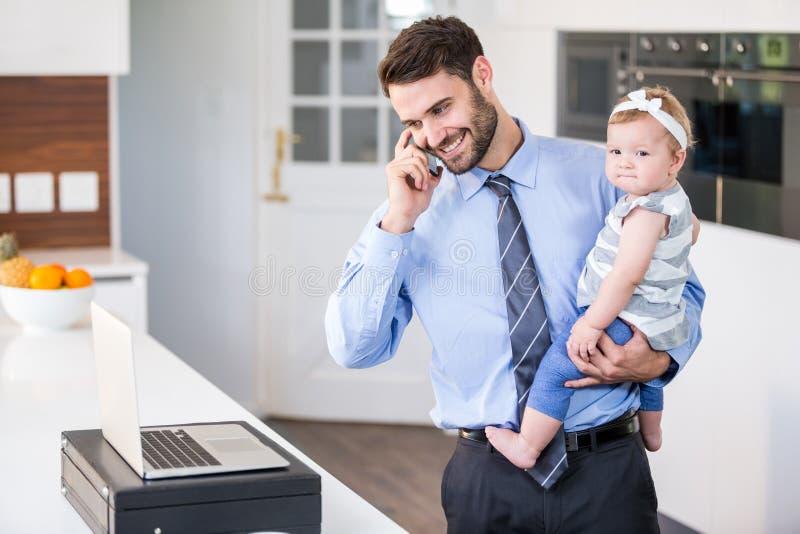 Бизнесмен говоря на мобильном телефоне пока носящ дочь стоковая фотография rf