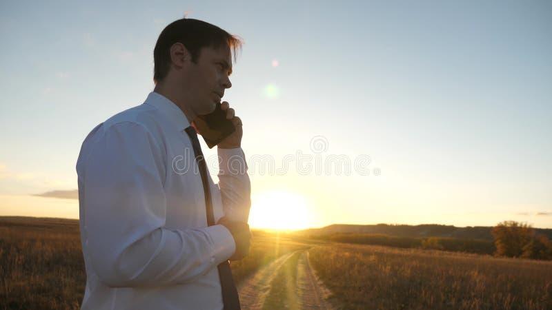 Бизнесмен говоря на смартфоне против неба человек в связи с планшетом в парке на заходе солнца говорить мобильный стоковое фото