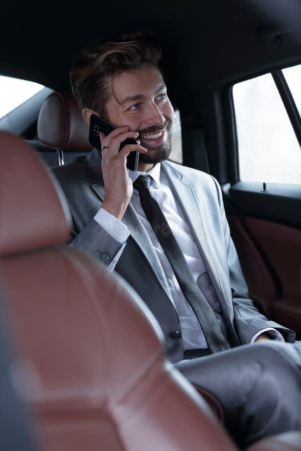 Бизнесмен говоря на телефоне в задней части стоковая фотография