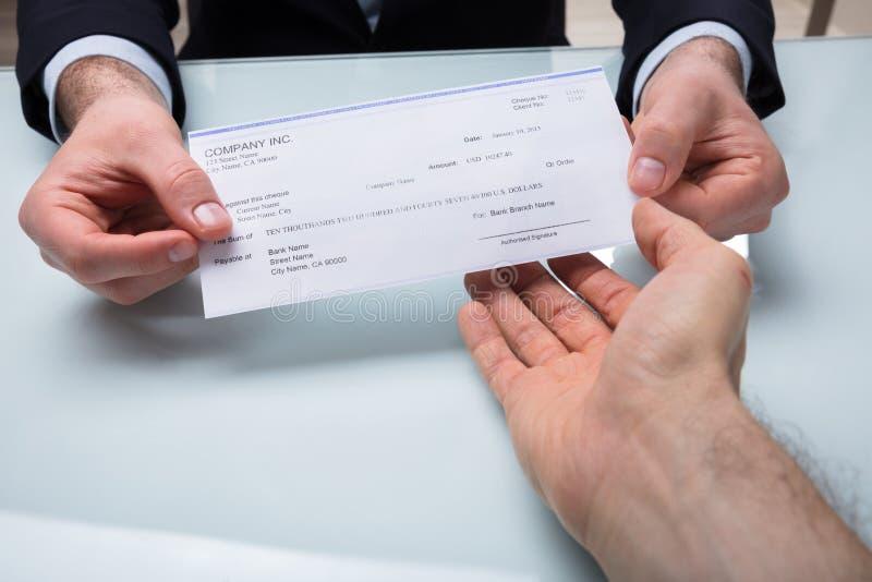 Бизнесмен давая чек к его коллеге стоковое изображение rf