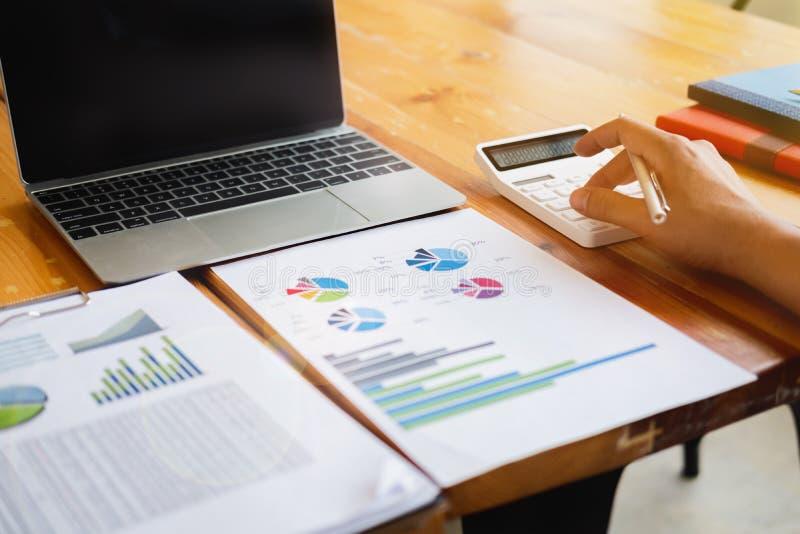 Бизнесмен делая вычисление с ручкой в руке, концепции финансов стоковое изображение