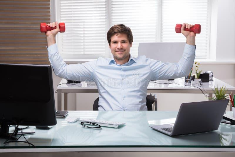 Бизнесмен делая тренировку с гантелью стоковое изображение