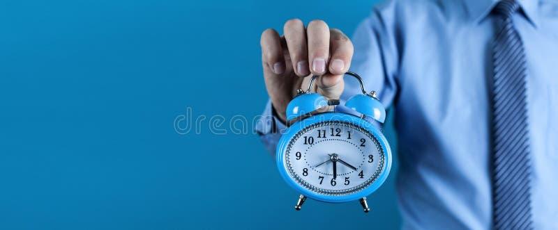Бизнесмен держа будильник владение домашнего ключа принципиальной схемы дела золотистое достигая небо к стоковая фотография rf