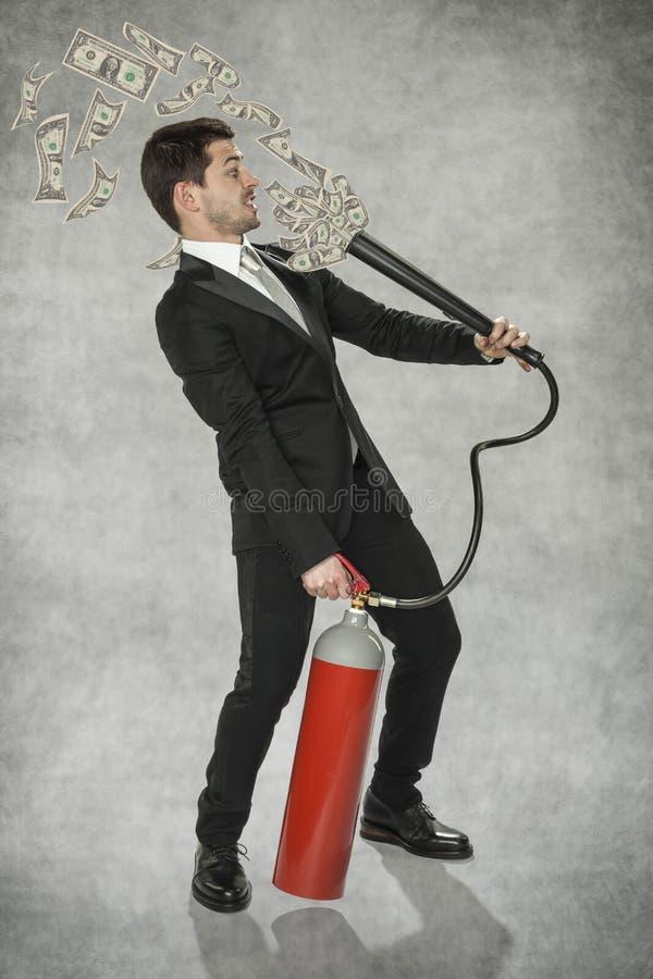 Бизнесмен держа деньг-делая машину стоковое изображение rf
