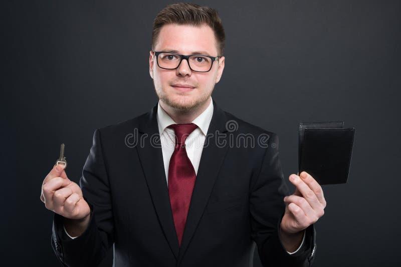 Бизнесмен держа ключевой и черный бумажник стоковая фотография