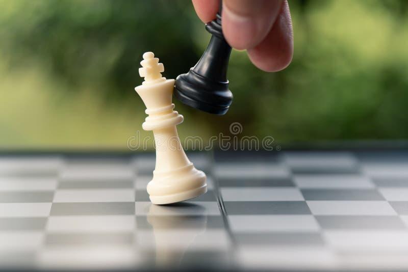 Бизнесмен держа короля Шахмат помещен на доске использование стоковое фото