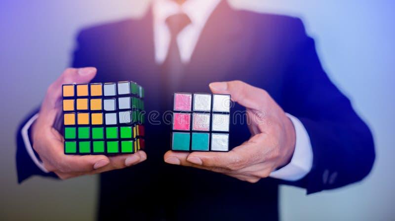 Бизнесмен держа куб Rubik стоковые фото