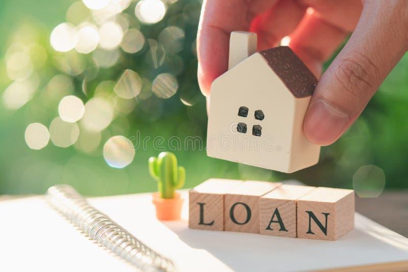 Бизнесмен держа модельную модель дома помещен на деревянном слове ЗАЙМЕ использование как концепция дела предпосылки и концепция  стоковая фотография