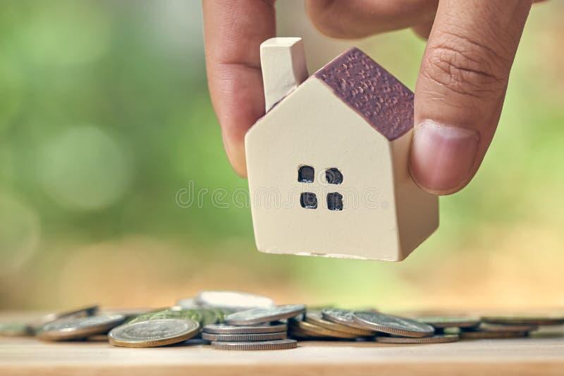 Бизнесмен держа модельную модель дома помещен на куче монеток использование как концепция дела предпосылки и концепция недвижимос стоковые изображения rf