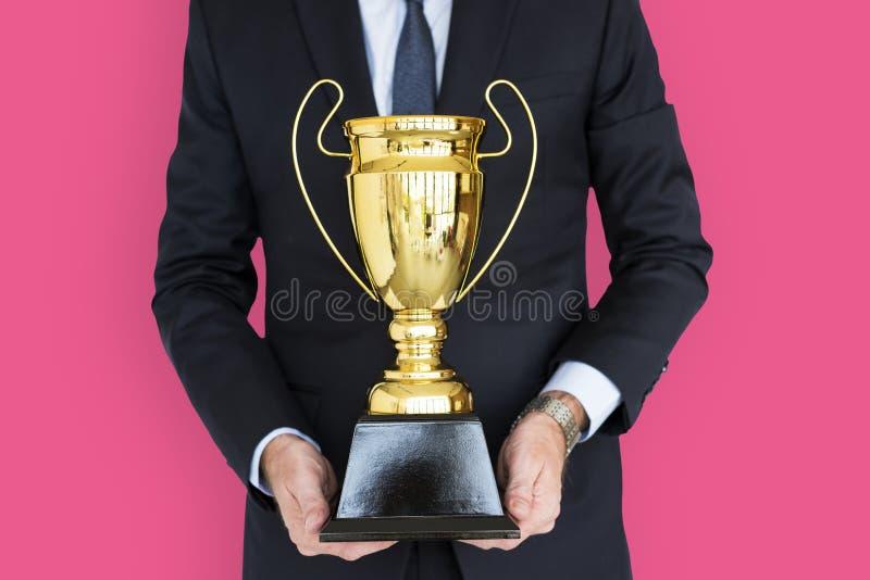 Бизнесмен держа награду трофея стоковые фотографии rf