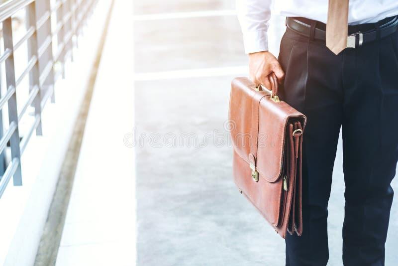Бизнесмен держа путешественников портфеля идя outdoors стоковое фото
