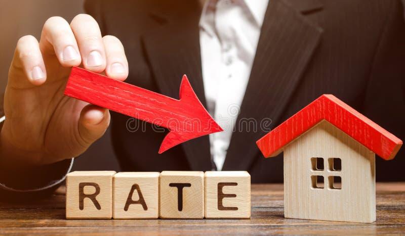 Бизнесмен держа стрелку спуска на деревянных блоках с тарифом и домом слова Низкий процент в ипотеках Уменьшение интереса стоковые изображения rf