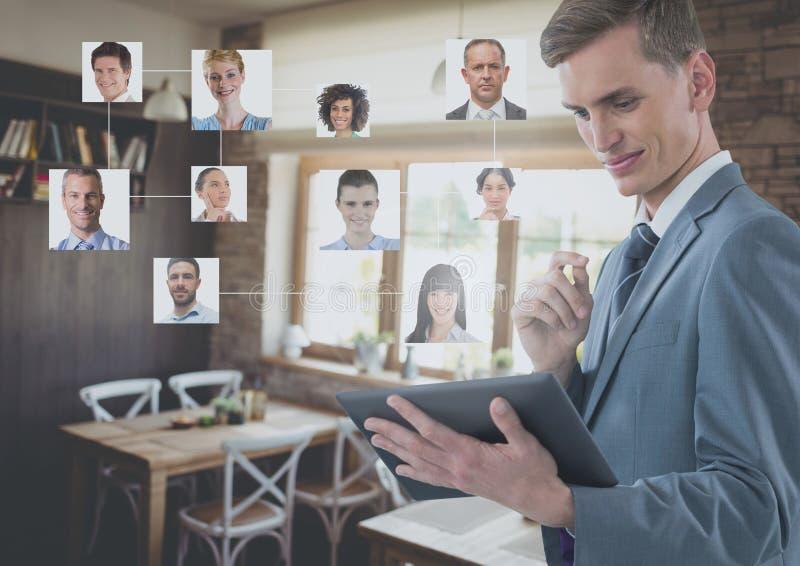 Бизнесмен держа таблетку с изображениями профиля ` s людей в ресторане кафа стоковые фото
