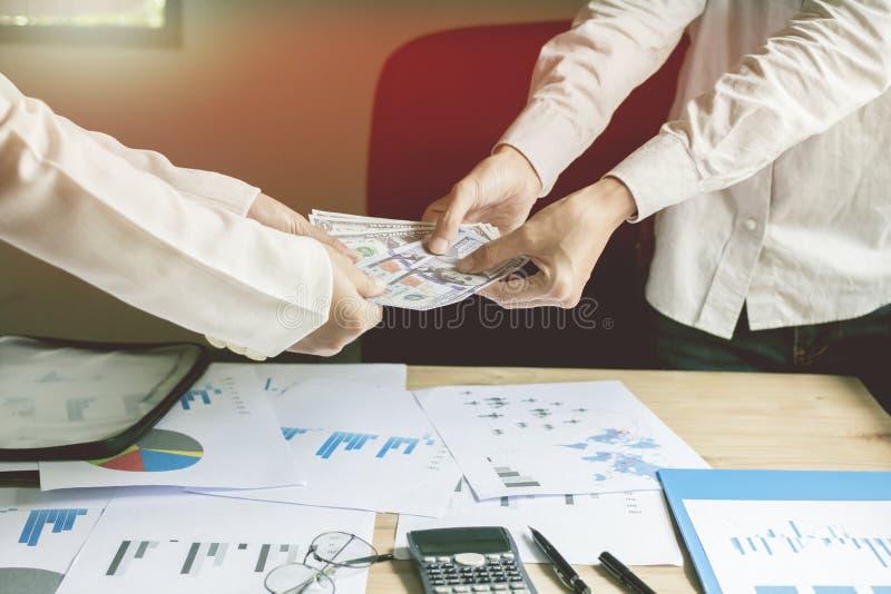 Бизнесмен держит банк с командой и бумаги на моем столе освещают предпосылку захода солнца стоковые изображения rf