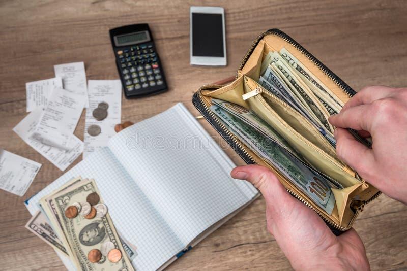 Бизнесмен держит бумажник с долларами на тетради предпосылки стоковые фотографии rf