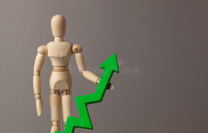 Бизнесмен держит зеленый цвет вверх по стрелке Вычет в подъеме индикаторов в деле за счет руководителя E стоковое изображение rf