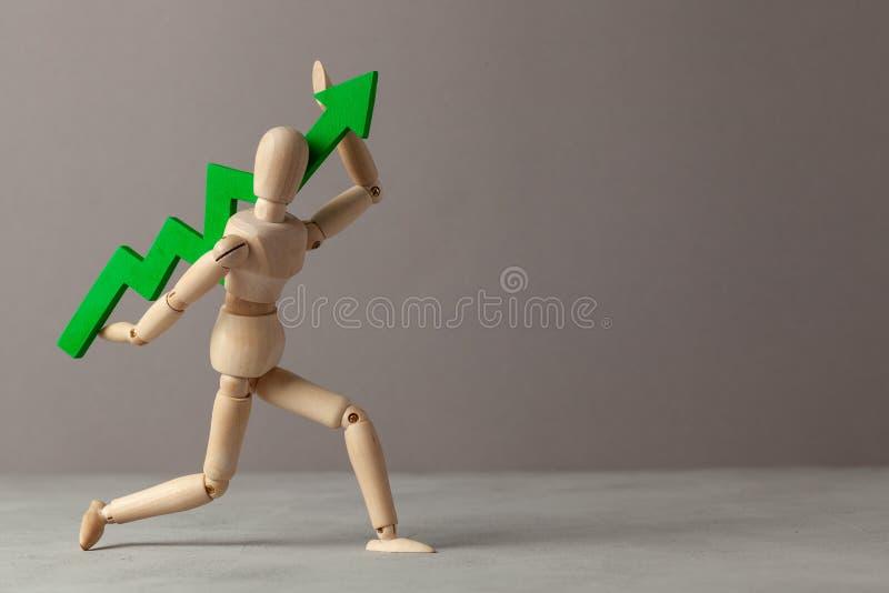 Бизнесмен держит зеленый цвет вверх по стрелке Вычет в подъеме индикаторов в деле за счет руководителя E стоковые фотографии rf