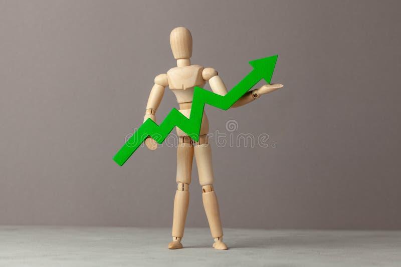 Бизнесмен держит зеленый цвет вверх по стрелке Вычет в подъеме индикаторов в деле за счет руководителя стоковое фото rf