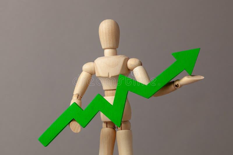 Бизнесмен держит зеленый цвет вверх по стрелке Вычет в подъеме индикаторов в деле за счет руководителя стоковые изображения rf