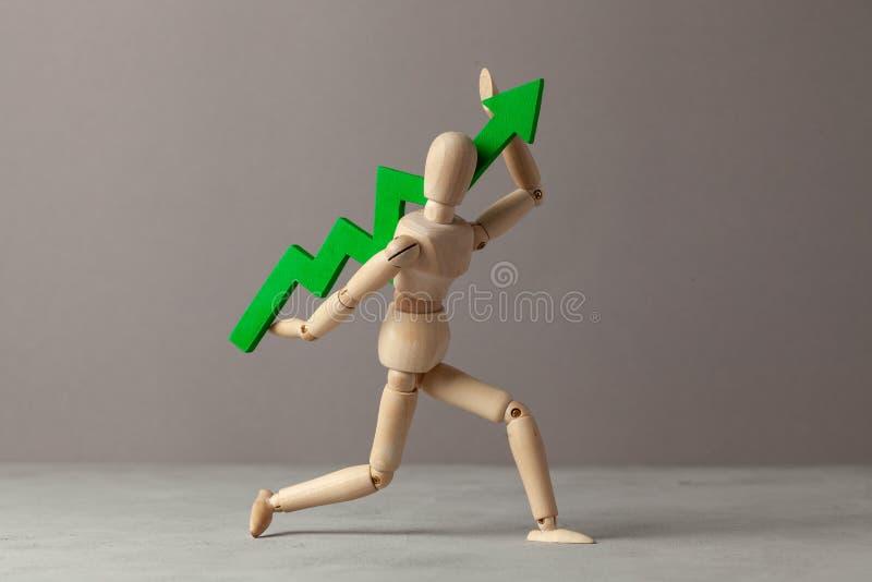 Бизнесмен держит зеленый цвет вверх по стрелке Вычет в подъеме индикаторов в деле за счет руководителя стоковое изображение rf