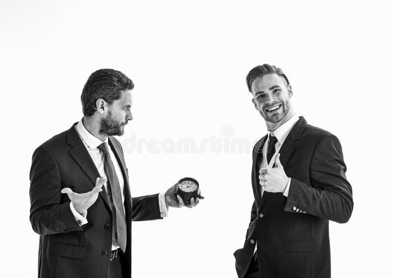 Бизнесмен держит часы с заботливой стороной и его партнером стоковые фото