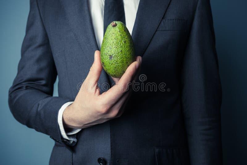 Бизнесмен держа авокадо стоковые фотографии rf